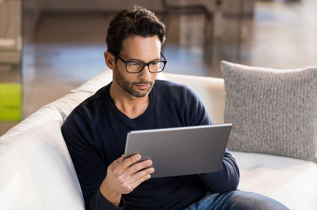 ネットの口コミをチェックする男性の画像