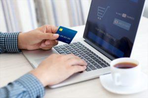 ネットショッピングでクレジット情報を入力する男性の画像