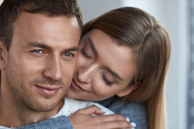 男性の首の香りに魅了される女性の画像