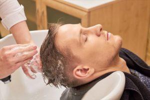 美容室のアミノ酸シャンプーで髪を洗う男性の画像