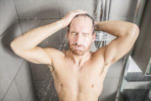 シャンプー前にお湯で予洗いする男性の画像