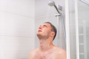落ちきるまでシャンプーを洗い流す男性の画像