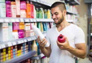 ドラッグストアで市販品のアミノ酸シャンプーを比べる男性の画像
