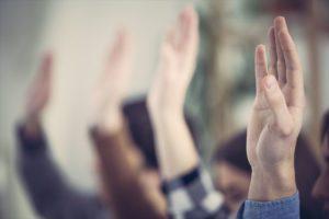 質問で手を挙げる人々の画像