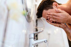 強い力でこすって顔を洗う男性の画像