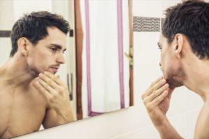 時分の肌質を鏡でチェックする男性の画像