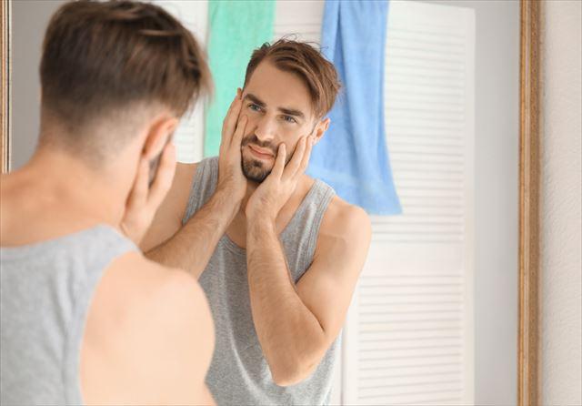 両頬を手で抑えながら鏡を見る男性の画像