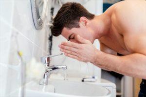 洗面所で洗顔する男性の画像