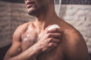 石けんで体を洗う男性の画像