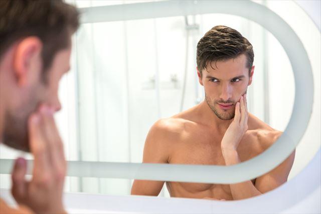 頬に乳液を塗る男性の画像